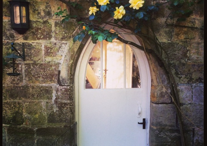 An ancient doorway crowned by spring roses and clematis at Pashley Manor Gardens, U.K.